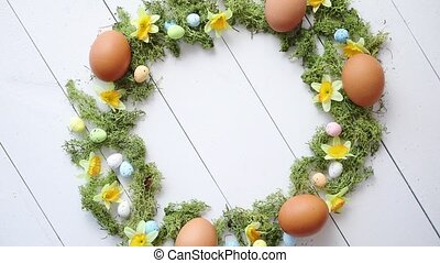Colorful decorative Easter eggs wreath on white wooden table...
