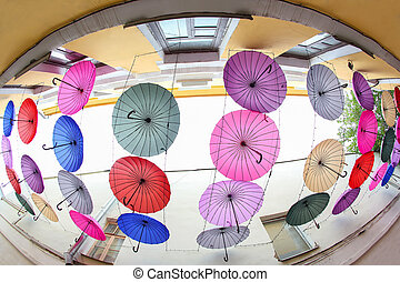 colorful decorative umbrellas hang between the buildings as protection from the sun and rain