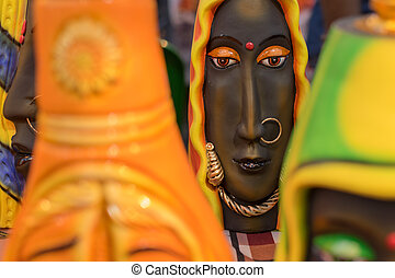 Colorful dolls made of clay, handicrafts on display.