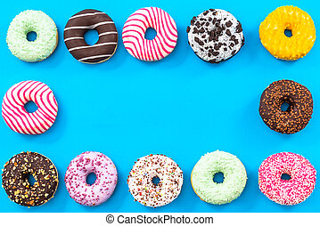 Colorful donuts border background, top view flat lay