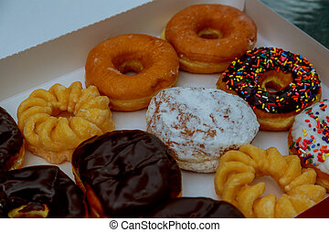Colorful donuts in box on wooden table.