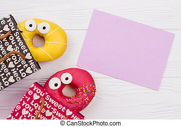 Colorful donuts in paper shopping bags.