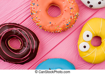 Colorful donuts on pink wooden background.