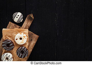 Colorful donuts on wooden table. Top view with copy space.
