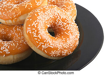 Colorful donuts. - Orange glazed donuts with white sprinkles...