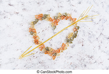 Colorful dry love pasta on white background. Top view