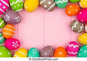 Colorful Easter egg frame against a pink wood background