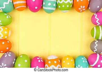 Colorful Easter egg frame against a yellow wood background
