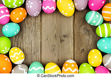 Colorful Easter Egg frame on a wood background