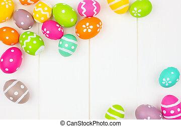 Colorful Easter Egg frame or corner border over a white wood background