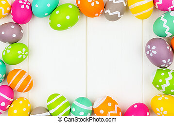 Colorful Easter Egg frame over a white wood background
