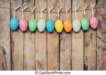 Colorful easter egg hanging on wood background