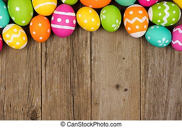 Colorful Easter egg top border against a rustic wood background