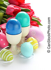Colorful easter eggs and pink tulips on white background