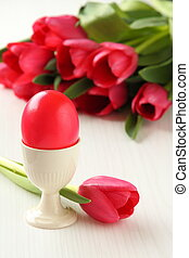 Colorful easter eggs and pink tulips on white wooden background