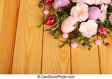 Colorful Easter eggs, candy, flowers, ribbon, grass on light...