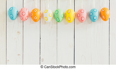 Colorful easter eggs hanging on rustic wooden white background with space.