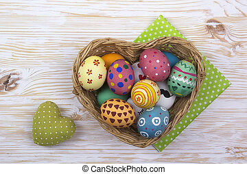 colorful easter eggs in a basket on wooden background