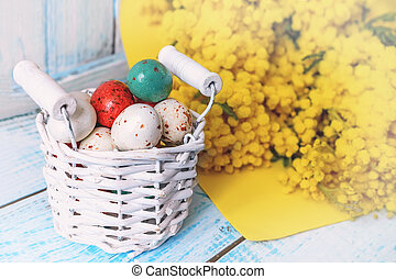 Colorful Easter eggs in a white wicker basket and Mimosa flowers on a wooden table.