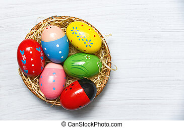 Colorful easter eggs in basket nest decoration on white wooden background top view