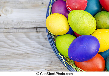 Colorful Easter eggs in basket on wooden background