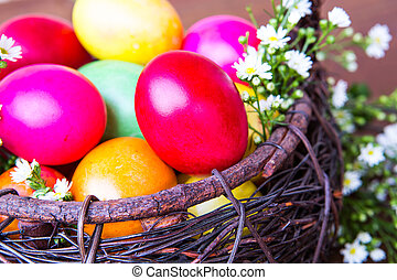 Colorful easter eggs in brown basket with flower