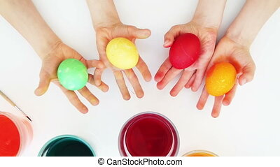 Colorful easter eggs in child hands. Top view