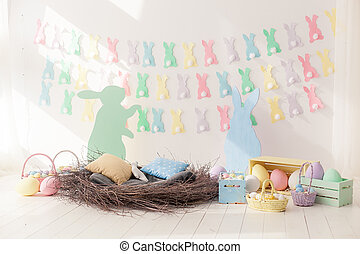 Colorful Easter Eggs in Nest from and baskets with space for copy text on wall background
