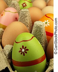 Colorful Easter eggs in the company of ordinary eggs