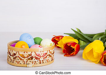 Colorful Easter eggs in wicker basket with tulips on white wooden background