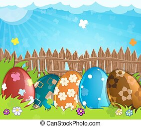 Colorful Easter eggs near a wooden fence in the meadow