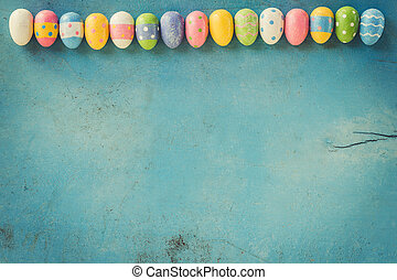 Colorful easter eggs on blue wood background with copy space.