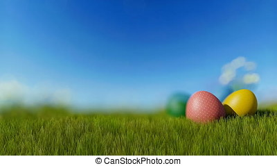 Colorful Easter eggs on green meadow over blue sky, focus in