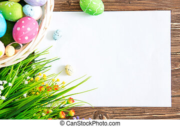 Colorful easter eggs on the nest in wooden basket with blank white paper on the pink background. Happy Easter