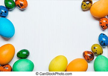 Colorful Easter eggs on wooden background with copy space.