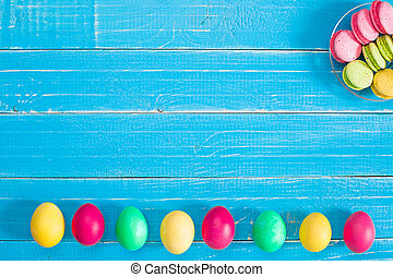 Colorful easter eggs on wooden board background with space.