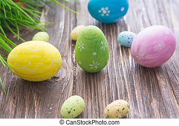 Colorful easter eggs with flowers on wooden board
