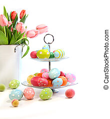 Colorful easter eggs with pink tulips on white