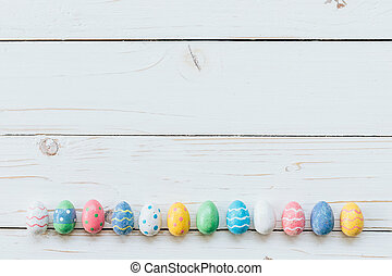 Colorful eggs easter on white wood background with space for text.