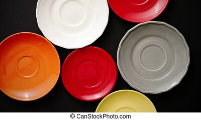 Colorful empty plates and saucers over black background....
