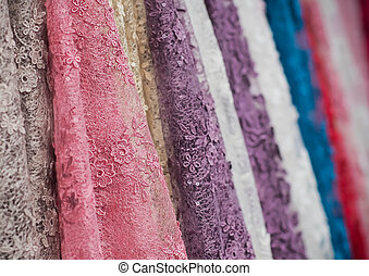 colorful fabric lace fabric rolls in textile shop industry.Rolls of bright colored fabric
