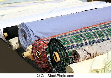 Colorful fabric rolls row in market shop
