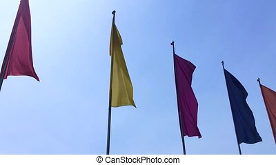 Colorful flags blowing on the wind on blue sky background
