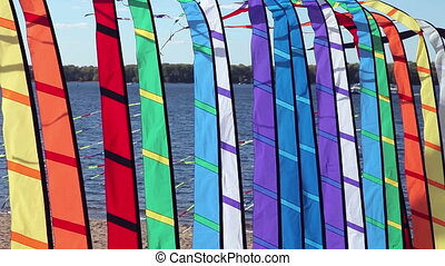 Colorful flags fluttering on the background of a large river