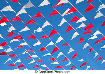 Colorful flags red and white on blue sky