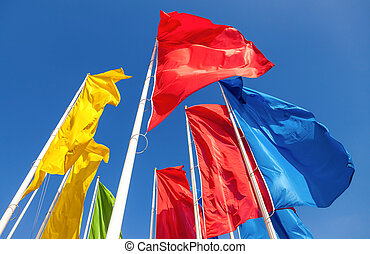 Colorful flags waving on blue sky background