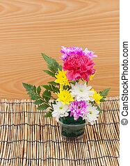 Colorful flower bouquet arrangement in vase on wood background