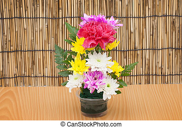Colorful flower bouquet arrangement in vase on wood background