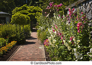 Colorful flower garden - Lush summer garden with paved path ...