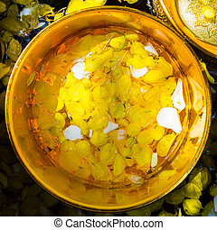 Colorful flower petals and water mixed with perfume in a golden bowl